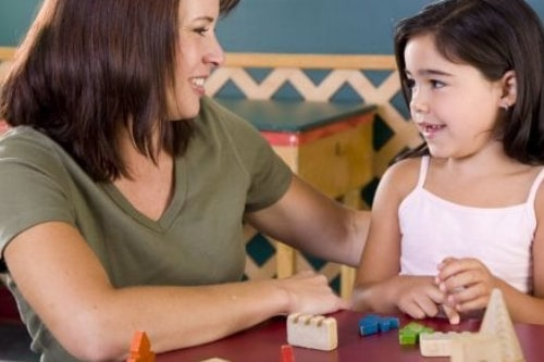 Smiling female school-based occupational therapist sits at table with elementary-aged girl as she works with blocks.