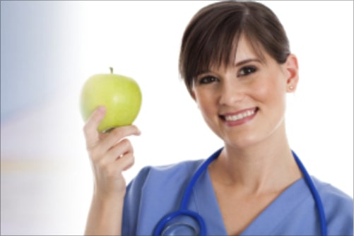 Female school nurse wearing blue scrubs and stethoscope draped around her neck holds up a green apple and smiles.