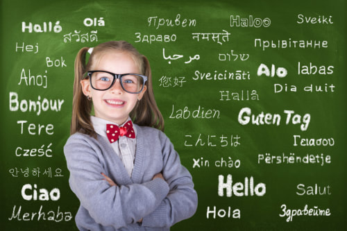 "Smiling elementary-aged girl poses with arms crossed in front of chalkboard covered with word ""Hello"" in multiple languages."