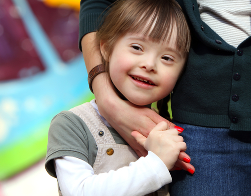 A young, smiling elementary-aged girl with short brown hair and facial characteristics of Down syndrome snuggles against a woman's waist.