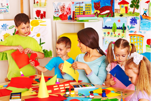Female occupational therapist cuts craft paper with two male and two female children in a colorful, art-filled classroom.