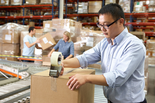 Young adult male seals a large box with packing tape as it moves down a conveyor belt in a shipping warehouse.