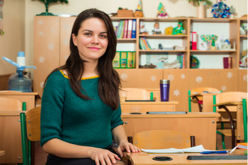 Female school-based therapist sits next to a desk in an empty school classroom with shelves in background, smiling confidently.