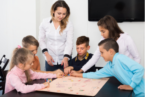 Female teacher supervises five young school children who gather around a table to play a speech therapy board game.