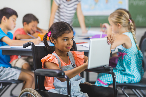Female elementary school student in wheelchair uses tablet computer while boys and girls sitting at table behind her write.