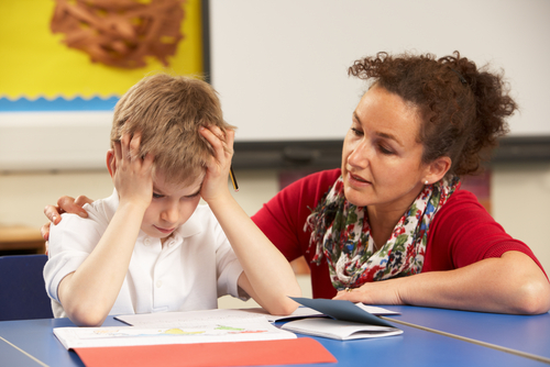 Female behavioral therapist sits next to upset elementary school boy in classroom and places her hand on his shoulder.